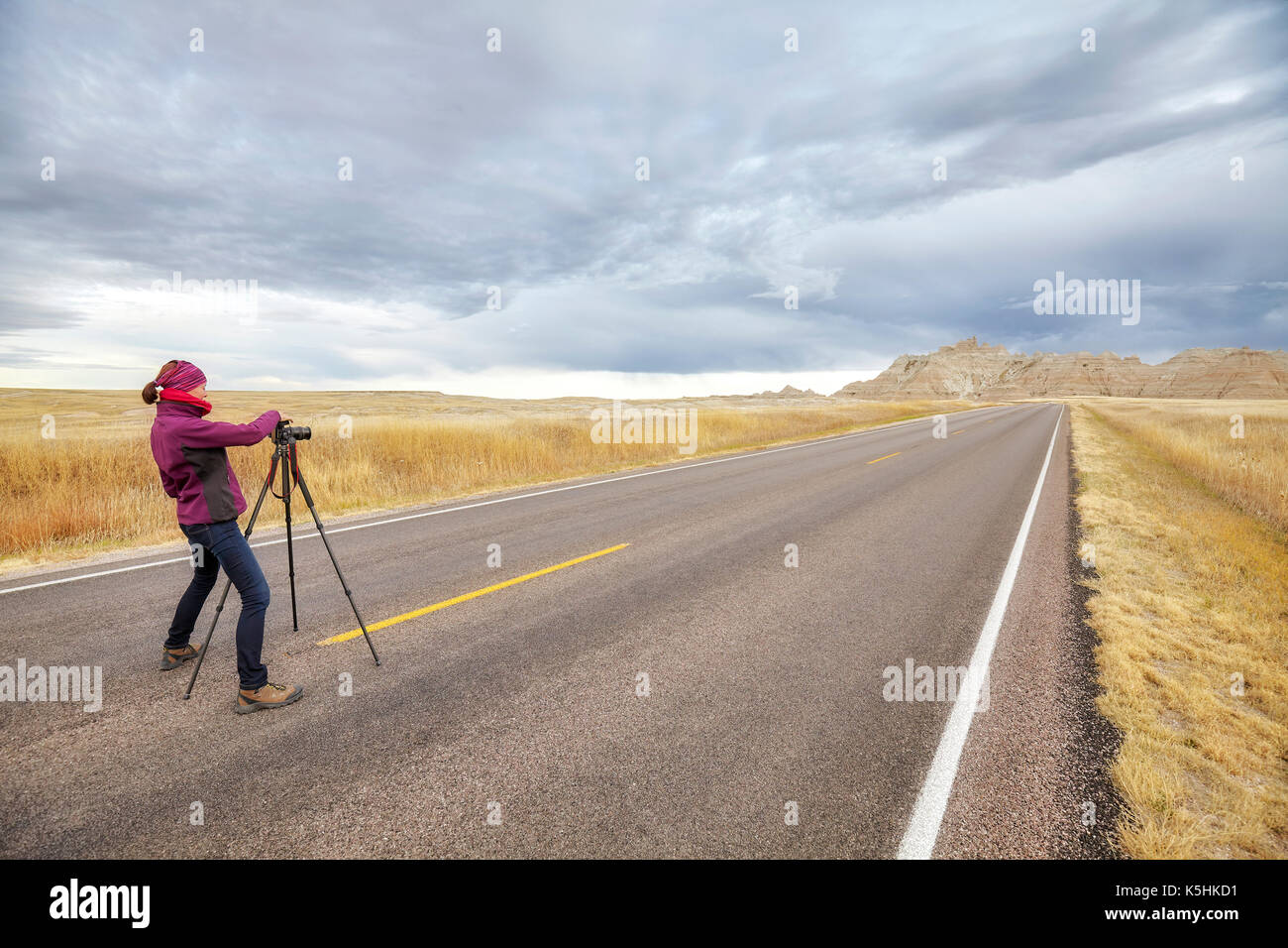 Landscape photographer takes pictures on an empty road with stormy sky, travel or work concept,  Badlands National - Stock Image