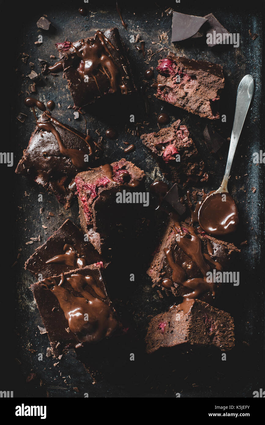 Chocolate cherry brownies decorated with melted chocolate on dark background. Table top view - Stock Image