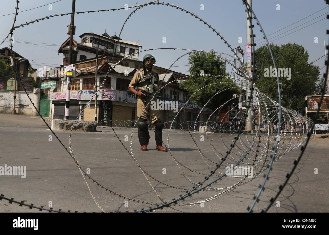 Srinagar, Indian-controlled Kashmir. 10th Sep, 2017. An Indian paramilitary trooper stands guard near a barricade - Stock Image