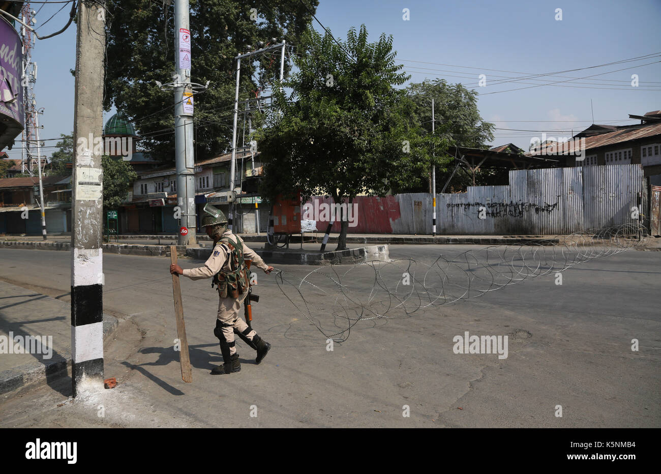 Srinagar, Indian-controlled Kashmir. 10th Sep, 2017. An Indian paramilitary trooper lays barbed wire on a road during - Stock Image