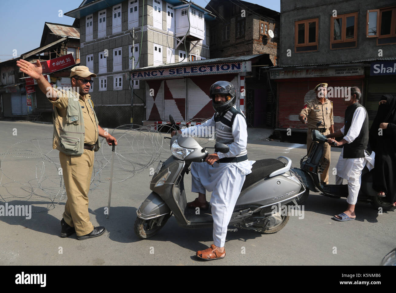 Srinagar, Indian-controlled Kashmir. 10th Sep, 2017. Indian policemen stop scooterists near a barricade during restrictions - Stock Image