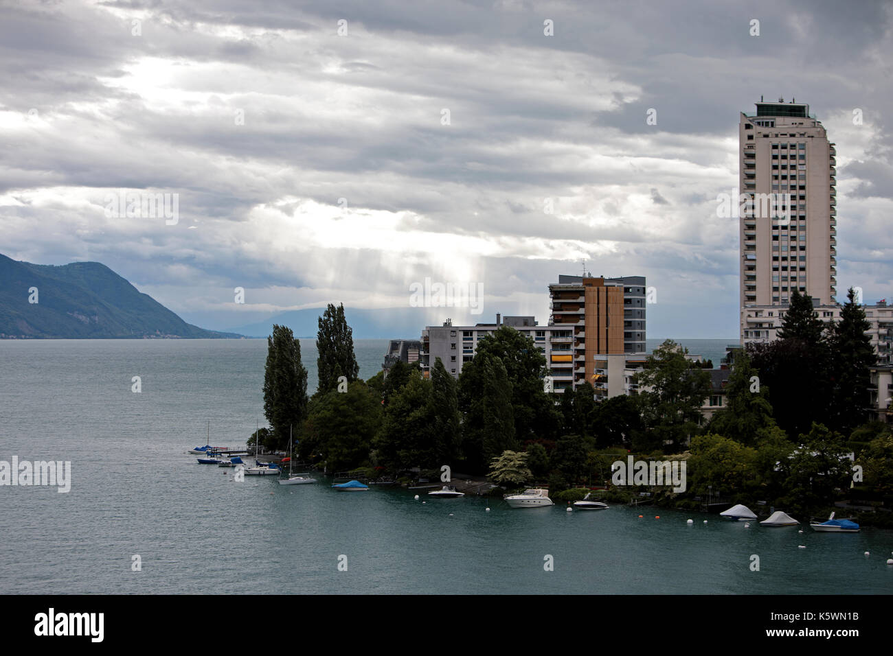 High rise apartment blocks in the center or Montreux on Lake Geneva in Switzerland. Boats and small yachts are moored - Stock Image