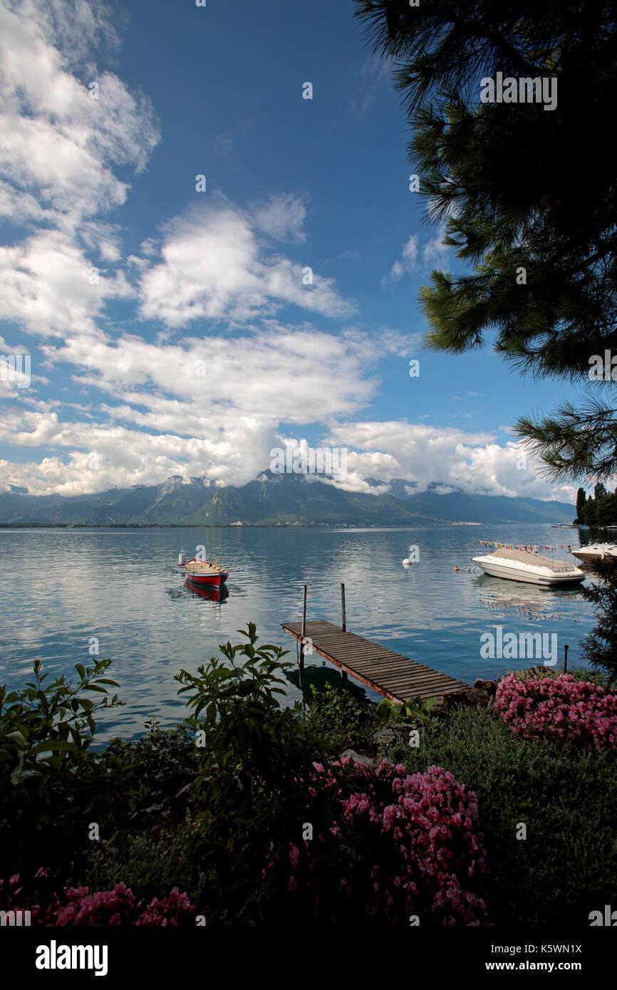 Walkway leading to rowing boat on Lake Geneva in Switzerland - Stock Image