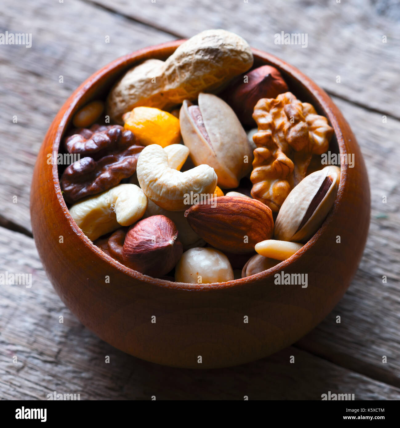 Mixed nuts in wooden bowl - Stock Image