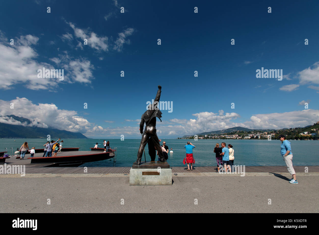 The statue of Freddie Mercury overlooking Lake Geneva in Montreux Switzerland. Freddie is surrounded by fans of - Stock Image