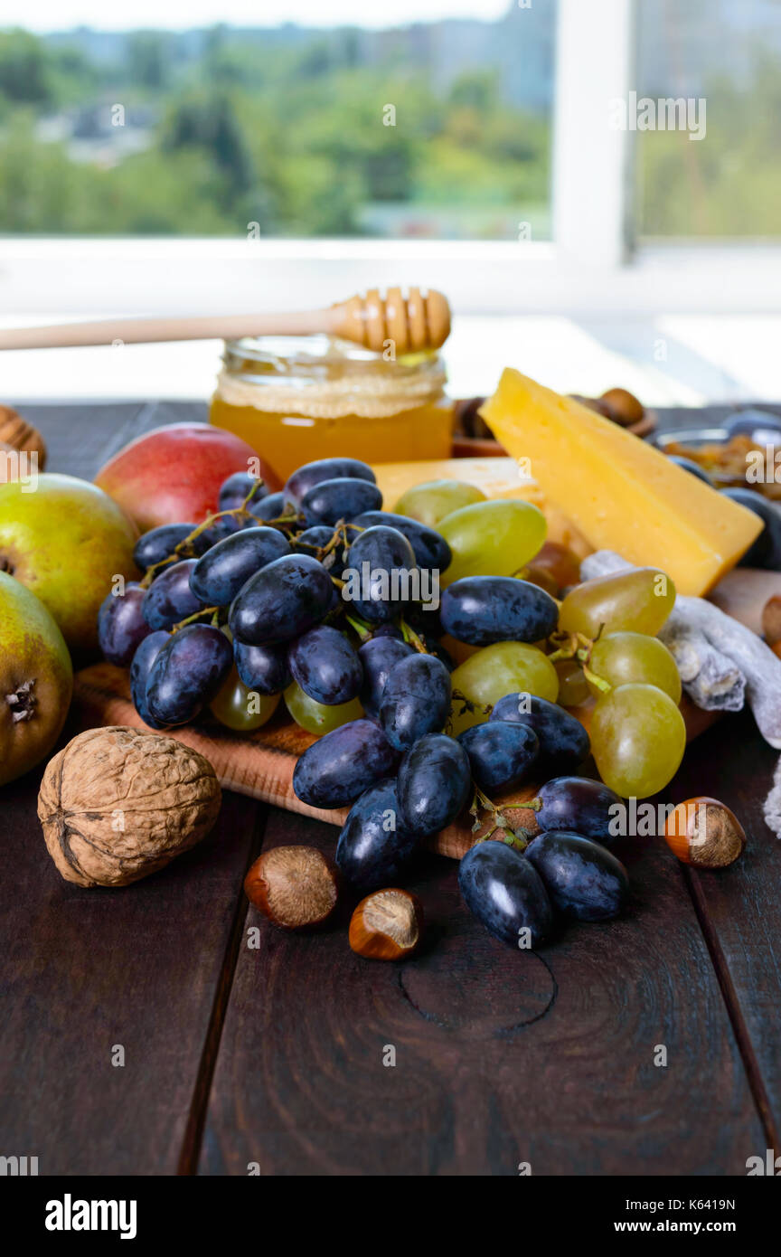 A set of products: grapes, nuts, honey, pears, cheese on a dark wooden table near the window. - Stock Image