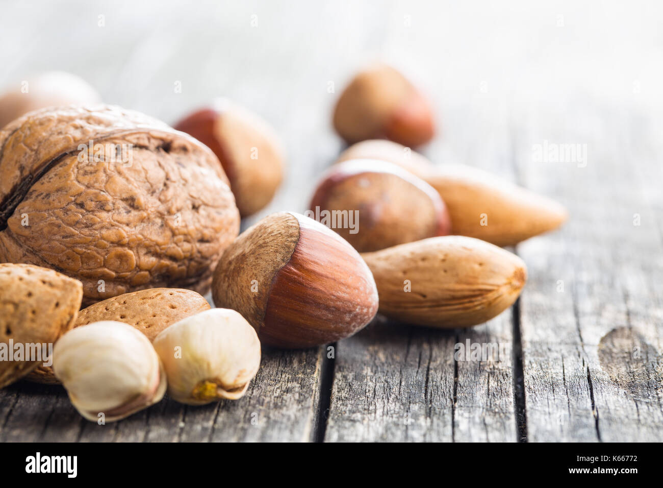 Different types of nuts in the nutshell. Hazelnuts, walnuts, almonds, pecan nuts and pistachio nuts on old wooden - Stock Image