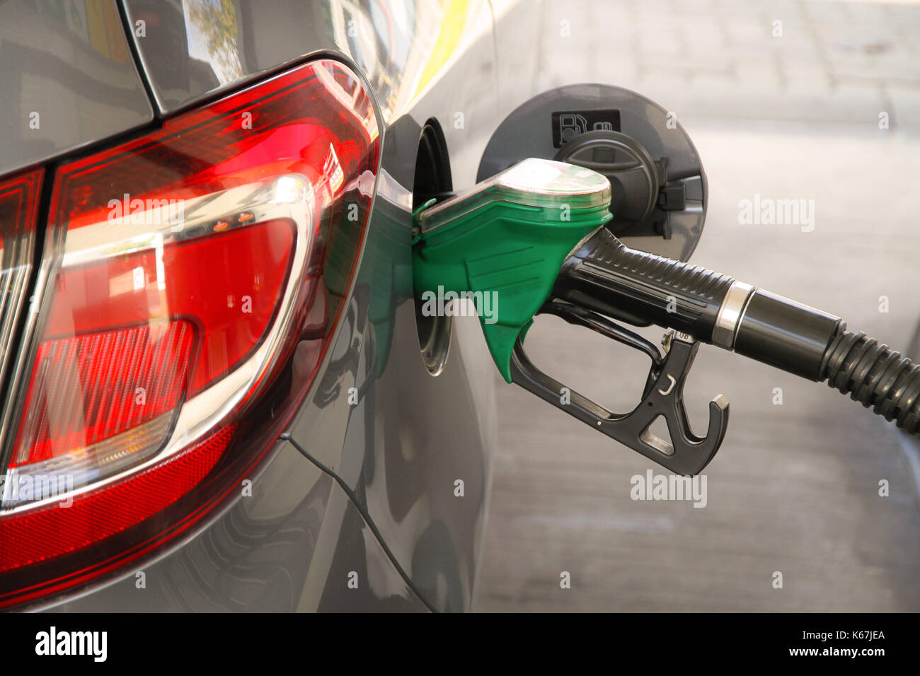 Car refueling at the petrol station.  Concept for use of fossil fuels (gasoline, diesel) in combustion engines and - Stock Image