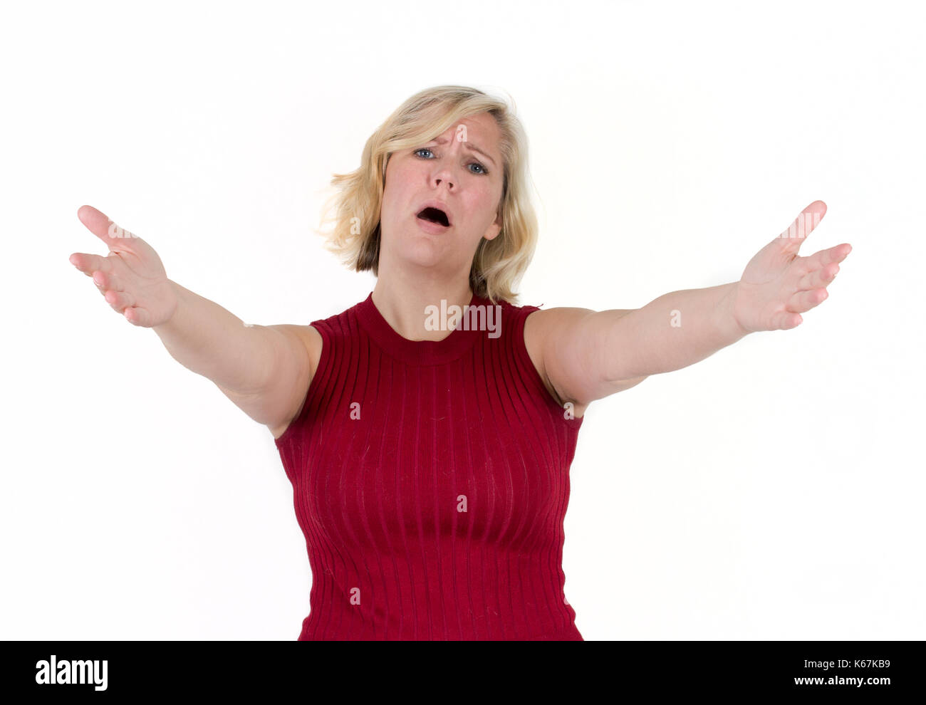a blond woman in studio background reaches arms and hands out, with a sad or pitying face - Stock Image