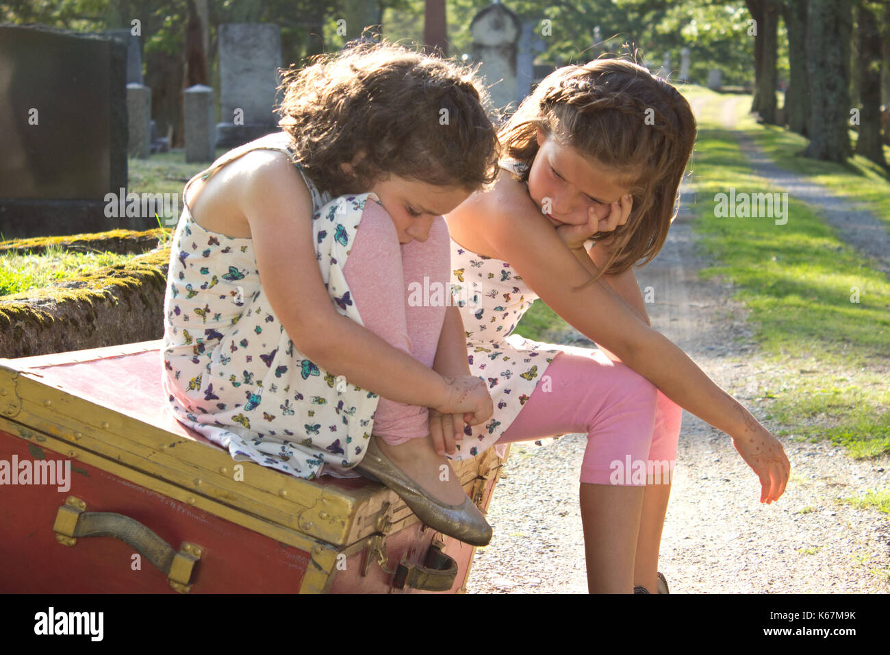 two sad brown haired girls sit on a red box in the cemetery with sad expressions - Stock Image