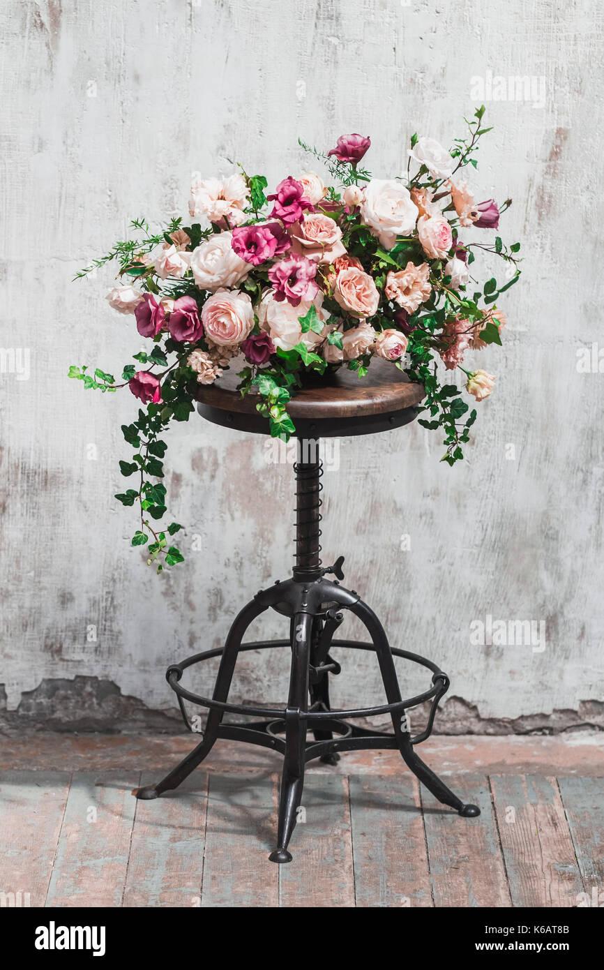 Wedding flower arrangement isolated on white painted background - Stock Image