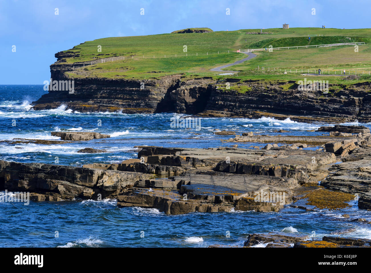 Waves breaking on foreshore on approach to Downpatrick Head, County Mayo, Republic of Ireland - Stock Image