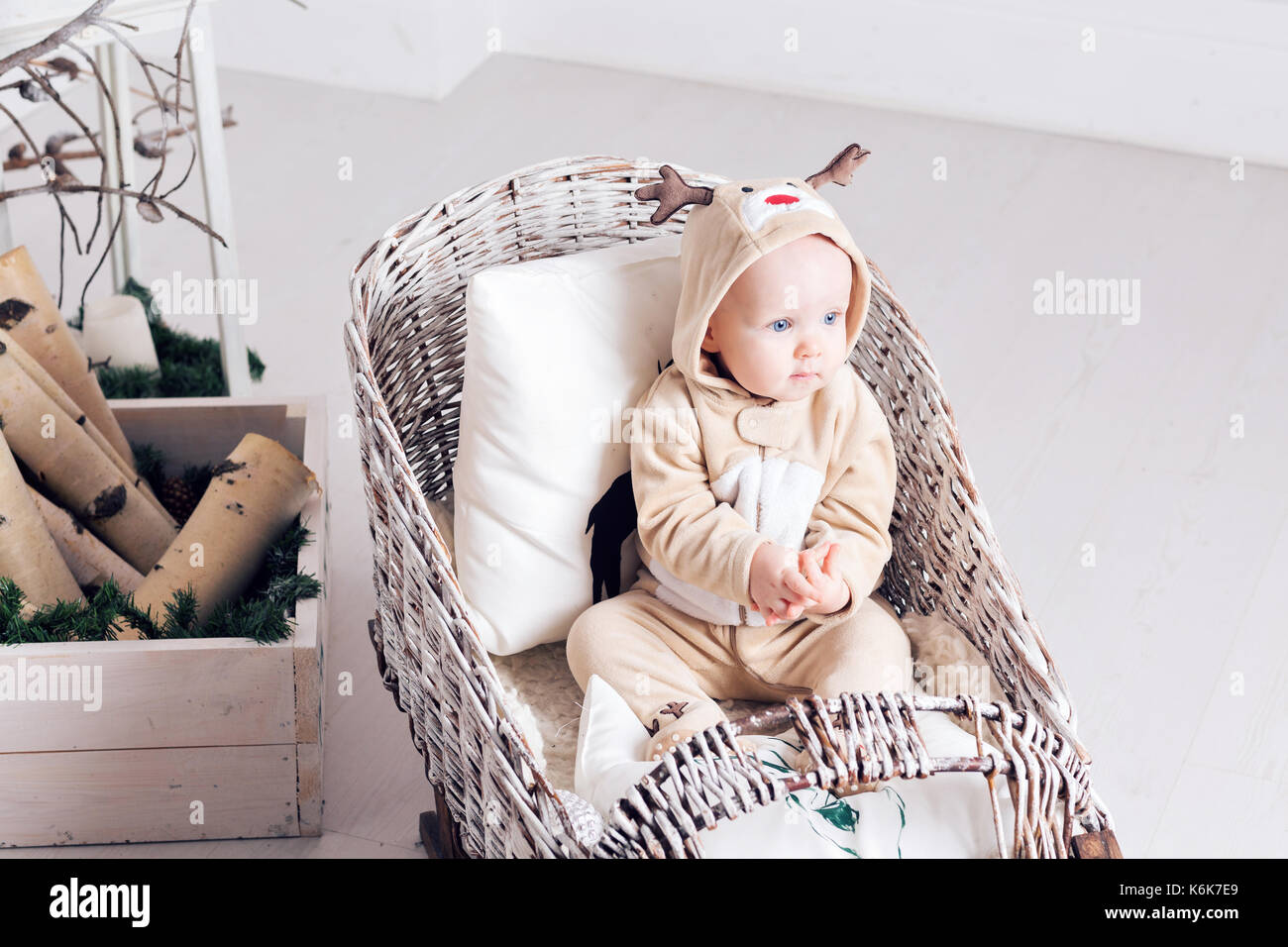 Christmas morning. Little girl in jumpsuit deer sitting in a toboggan. - Stock Image