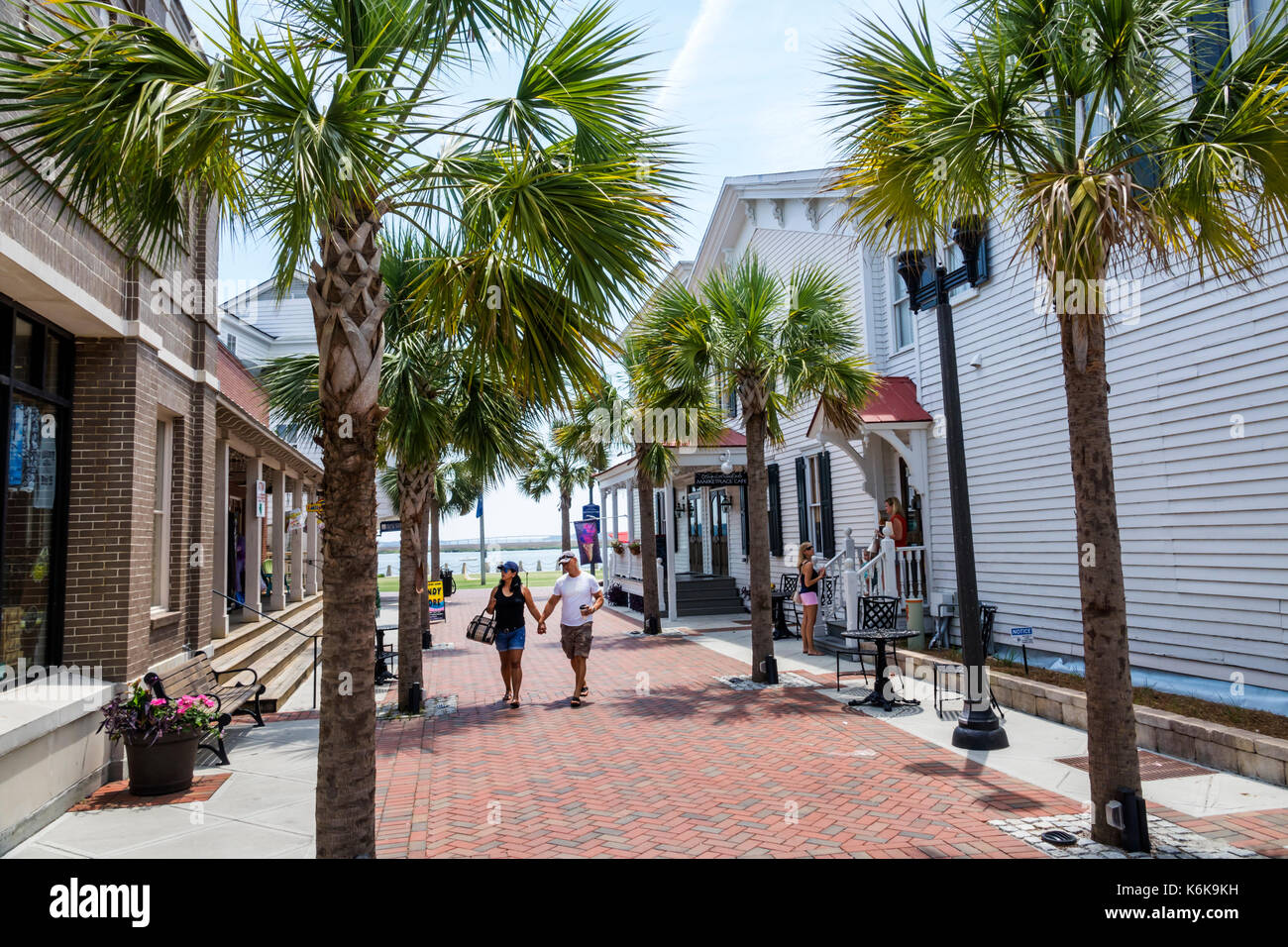 Beaufort South Carolina SC Bay Street Historic Downtown waterfront stores shops alley couple walking palm trees - Stock Image