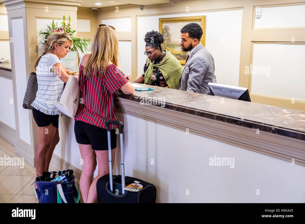 Charleston South Carolina SC Historic Downtown Francis Marion Hotel front desk check in guest clerk Black man woman - Stock Image