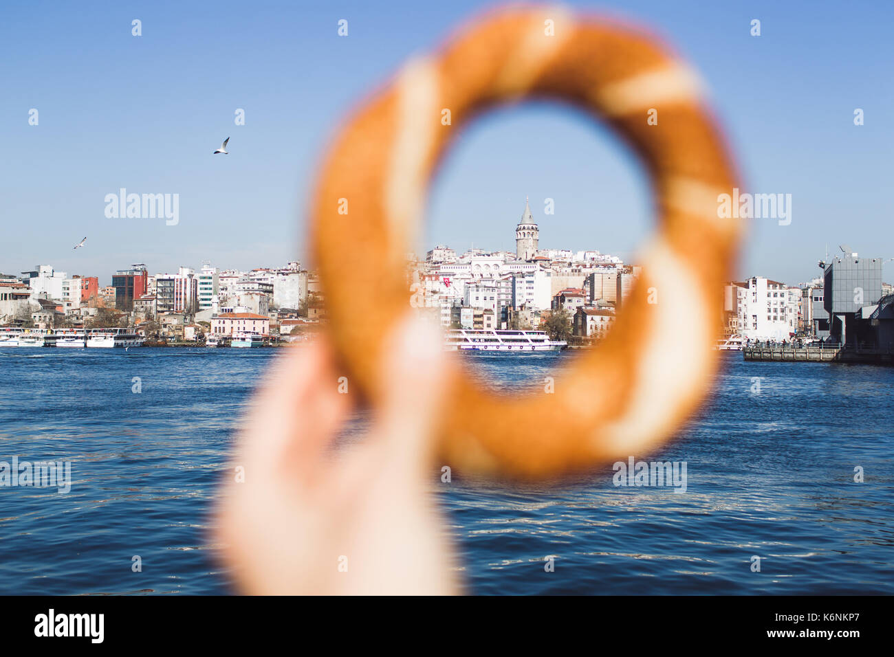 Woman hand holding a traditional Turkish simit on sea background and Galata Tower - Stock Image
