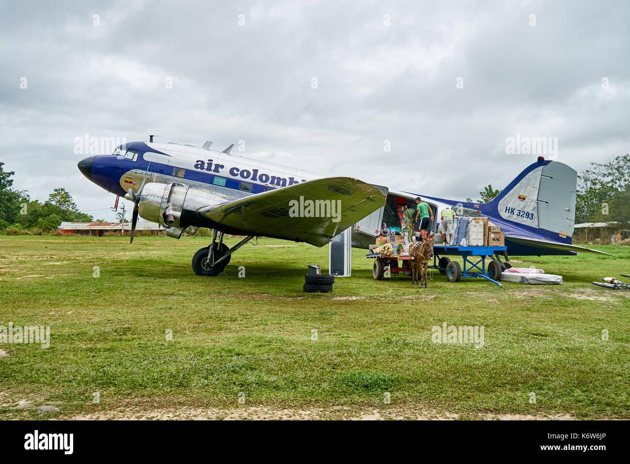 old Douglas DC-3 propeller plane loaded from donkey carriage , Serrania de la Macarena, La Macarena, Colombia, South - Stock Image