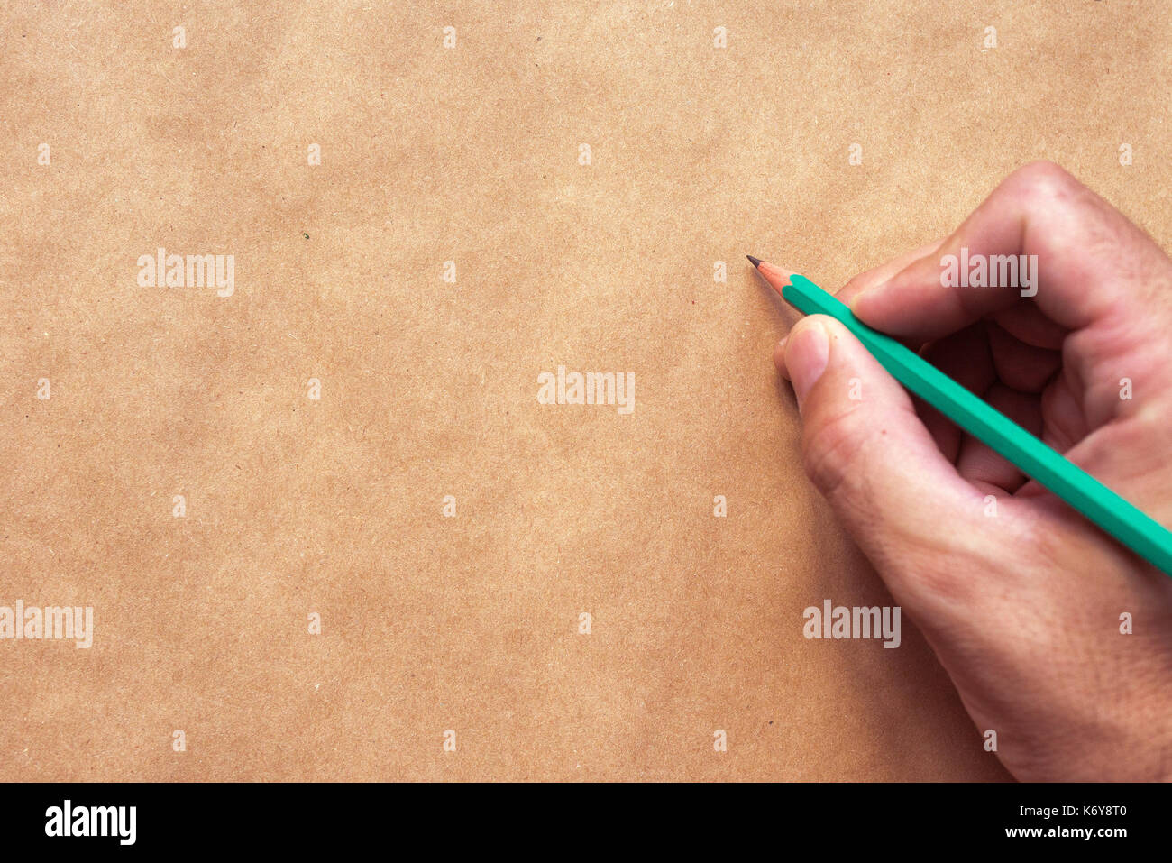 Male illustrator and sketch artist drawing with pencil, top view of  hand close up with selective focus - Stock Image