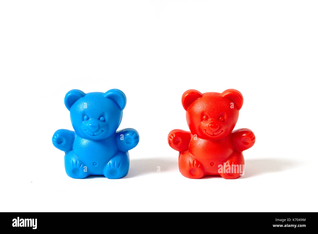 Small red and blue plastic toy bears isolated on white background - Stock Image