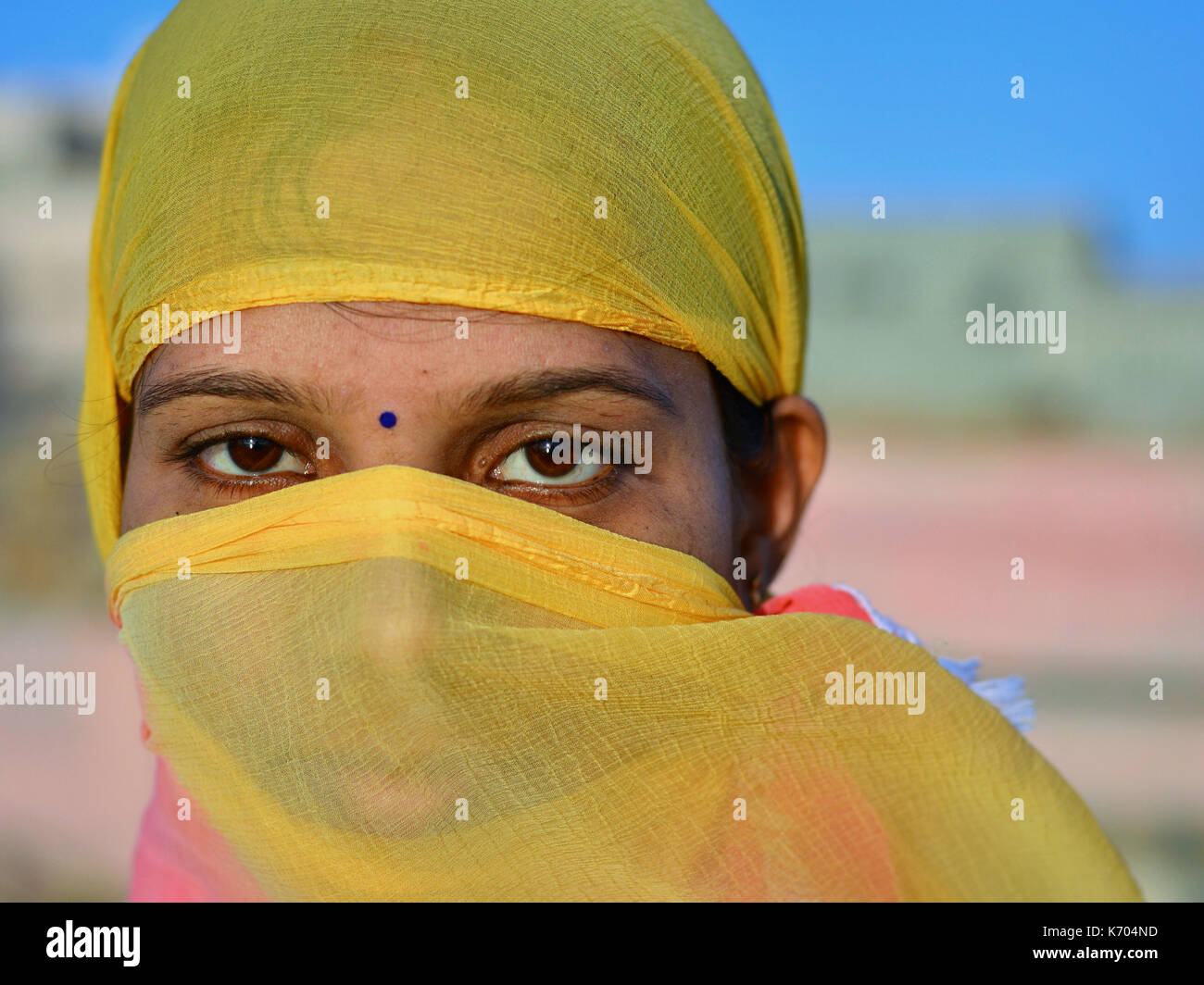 Pretty, young Indian woman, covering her hair and face with a trendy secular, half-sheer yellow headscarf; Dwarka, - Stock Image