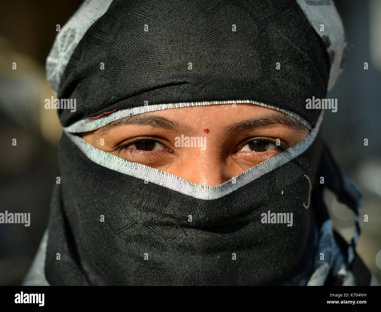 Young Indian woman with beautiful eyes, covering her hair and face with a trendy secular, black headscarf; Junagadh, - Stock Image