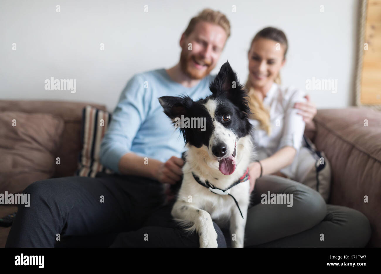 Beautiful couple relaxing at home and loving their dog - Stock Image