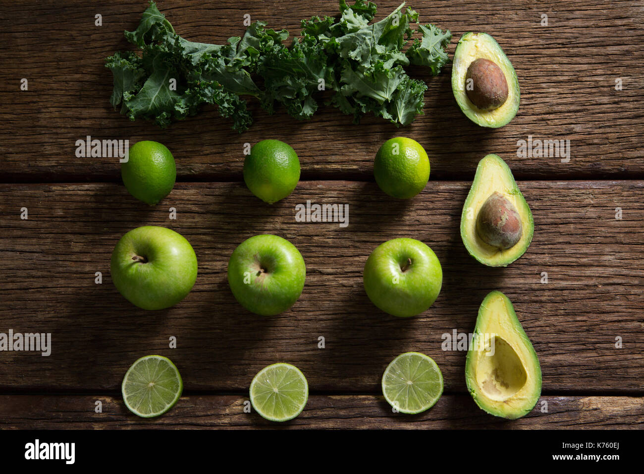 Overhead of mustard greens, lemon, avocado and green apple arranged on wooden table - Stock Image