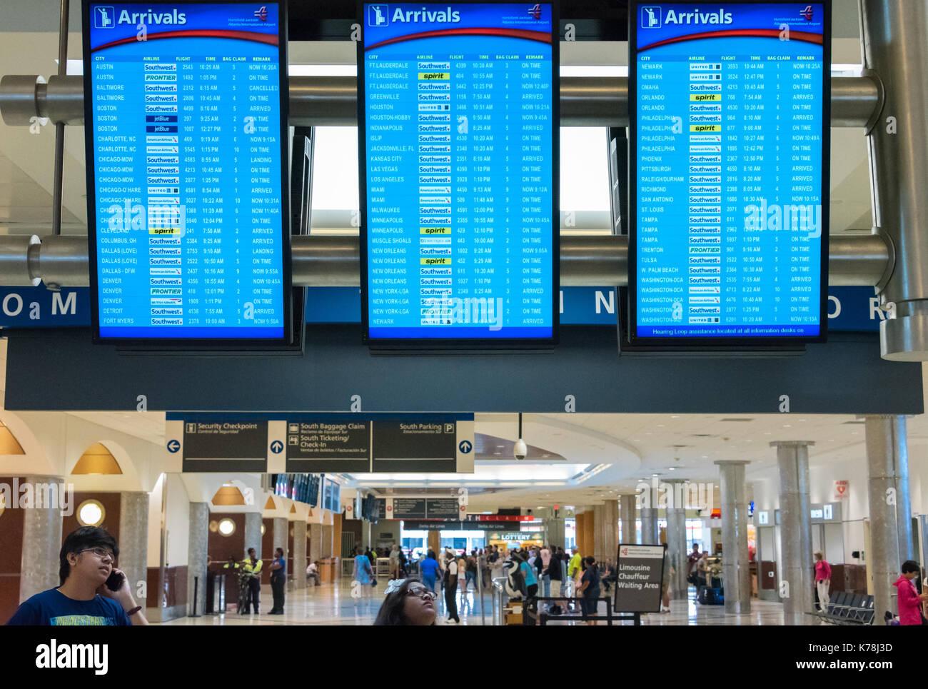 People checking flight arrival display boards at Hartsfield-Jackson Atlanta International Airport in Atlanta, Georgia. - Stock Image