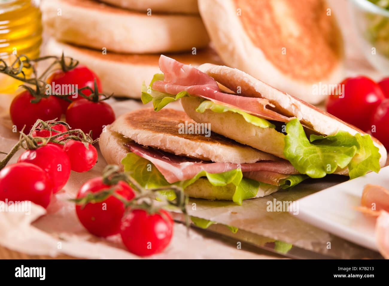 Tigella bread stuffed with ham and lettuce. - Stock Image