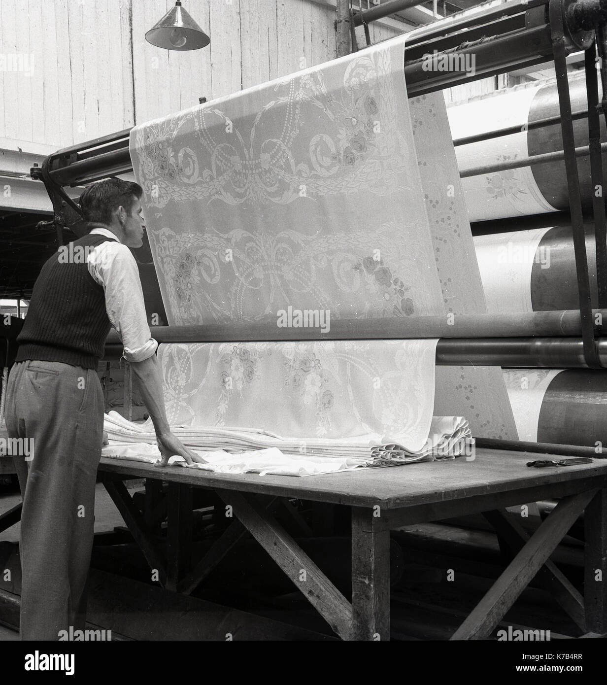 1950s, historical, man checking the printing of rolls of Irish linen, Northern Ireland. - Stock Image