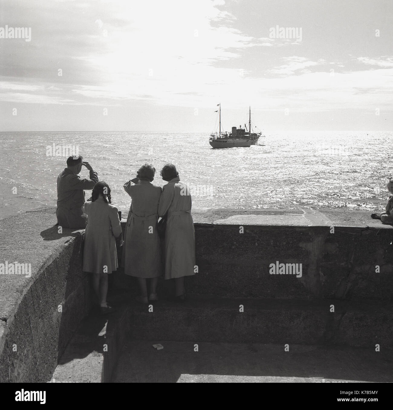 1950s, historical, man, women and child stand at jetty looking out at two boats in the distance. - Stock Image