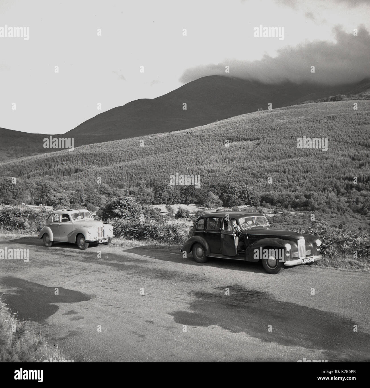 1950s, historical, two saloon cars parked up on a quiet country road in Northern Ireland, to take in the spectacular - Stock Image