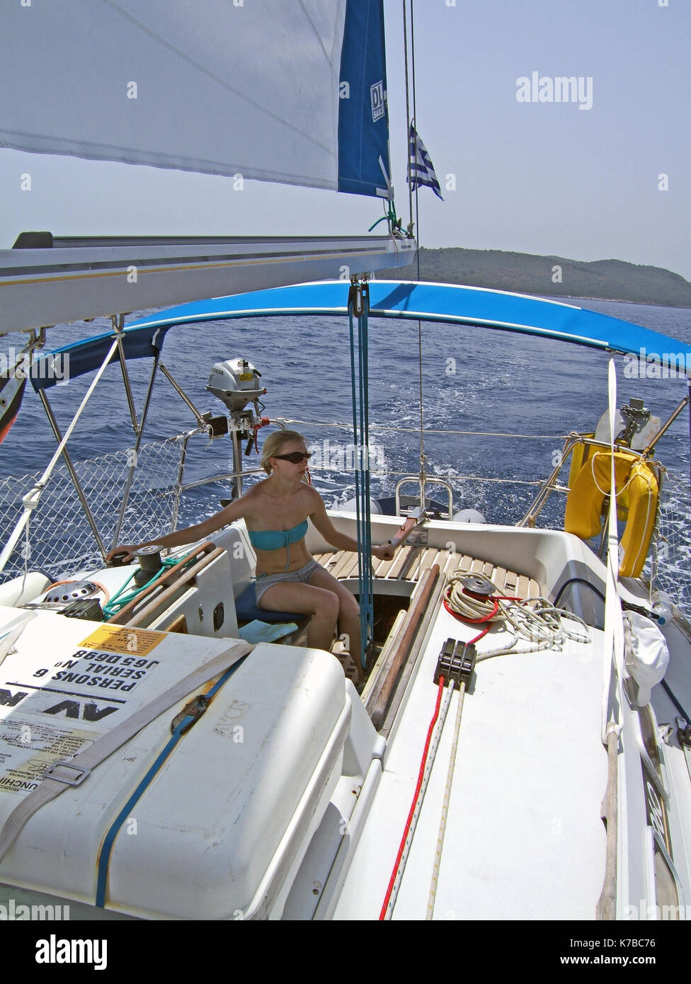 young woman sailing single handed in blue water yacht - Stock Image