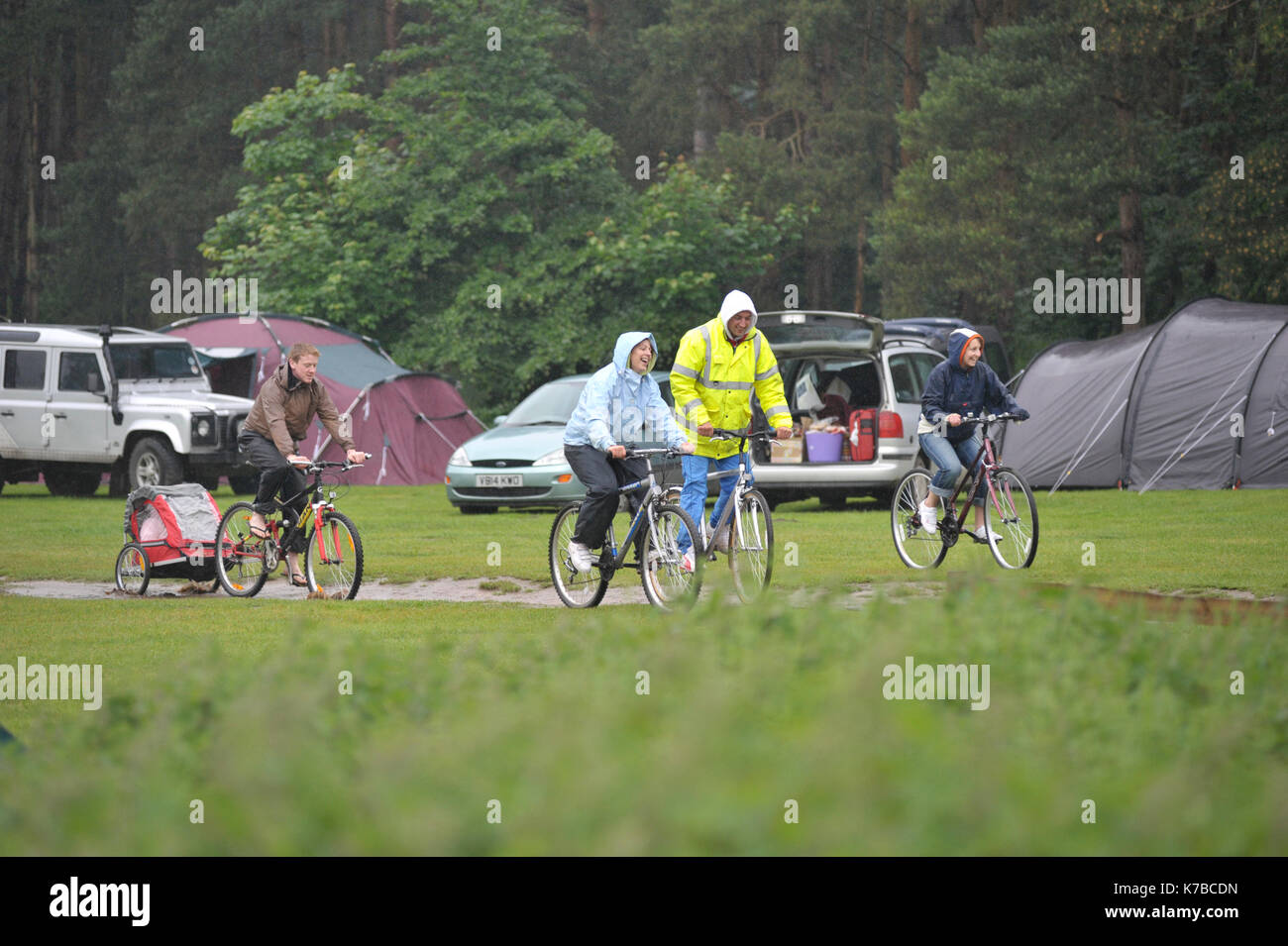 family cycling in the rain on camping holiday - Stock Image