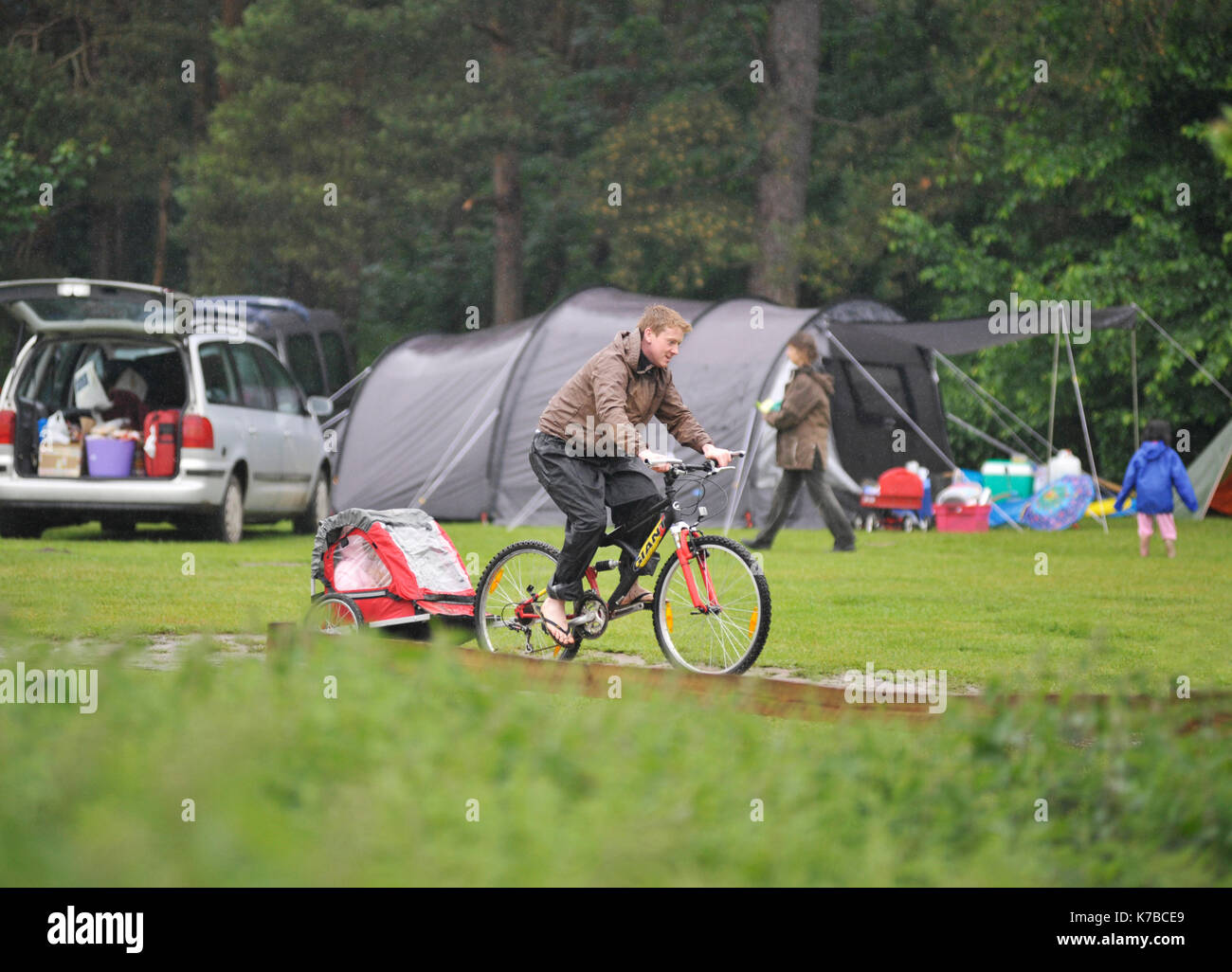 father towindg child behind bike in small trailer - Stock Image