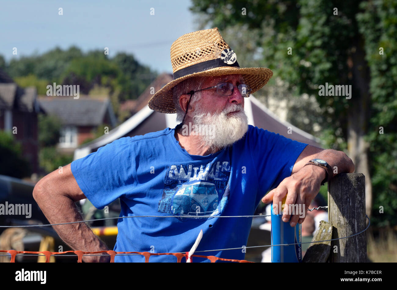 man with straw hat and white beard leaning on fence post in the sun - Stock Image