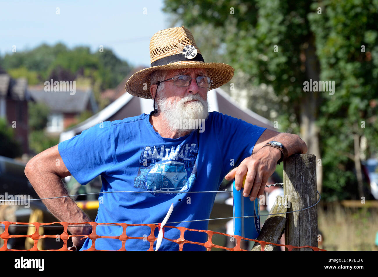 older man with straw hat leaning on fence post - Stock Image
