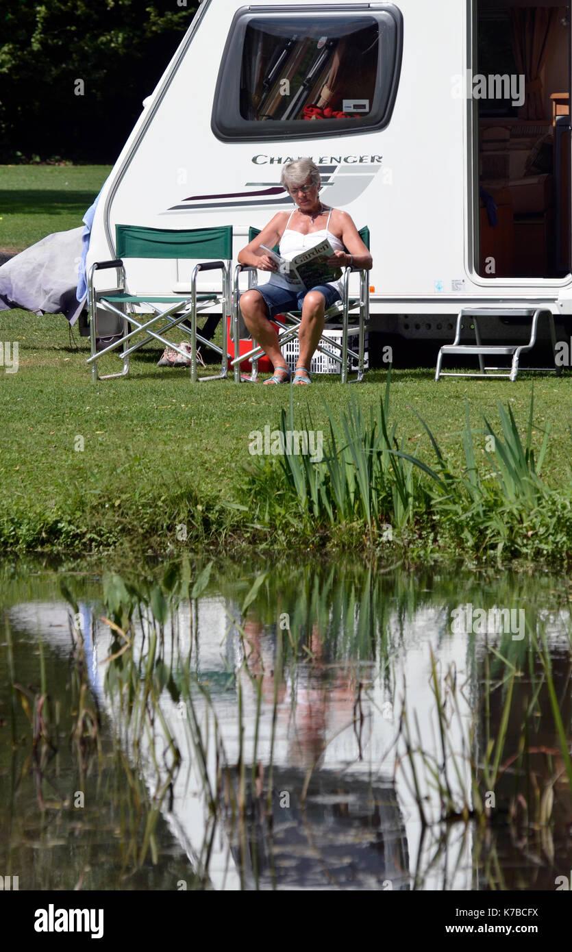 woman sitting reading outside caravan - Stock Image