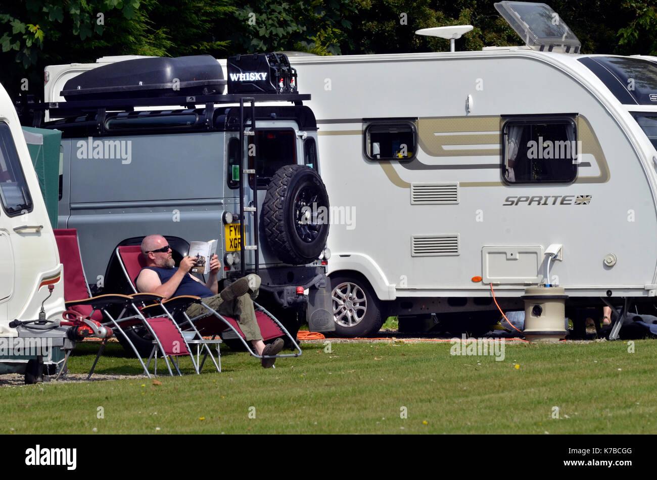man on holiday  reading outside caravan - Stock Image