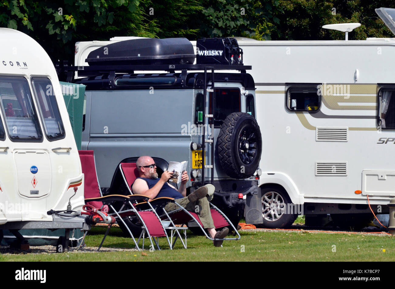 man on holiday sitting relaxing reading a book outside caravan - Stock Image