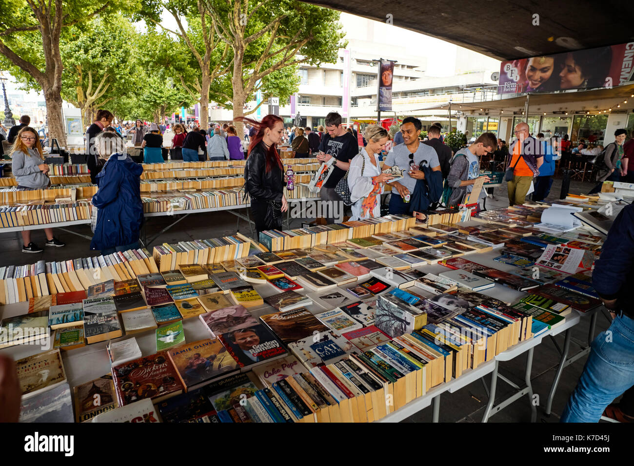 People choosing books at the Southbank under Waterloo Bridge on a Sunday - Stock Image