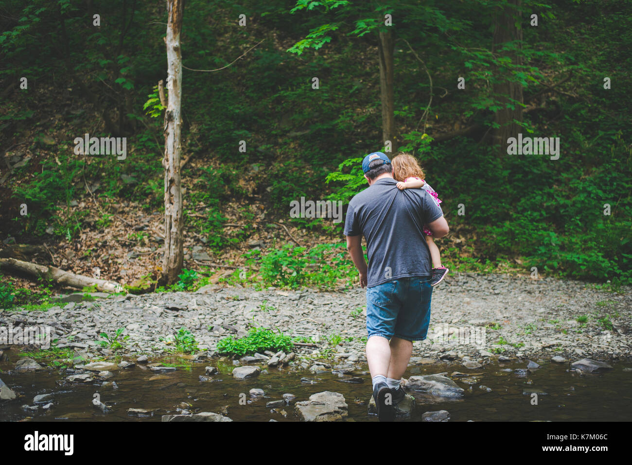 A father carries his daughter during a hike in the woods. - Stock Image