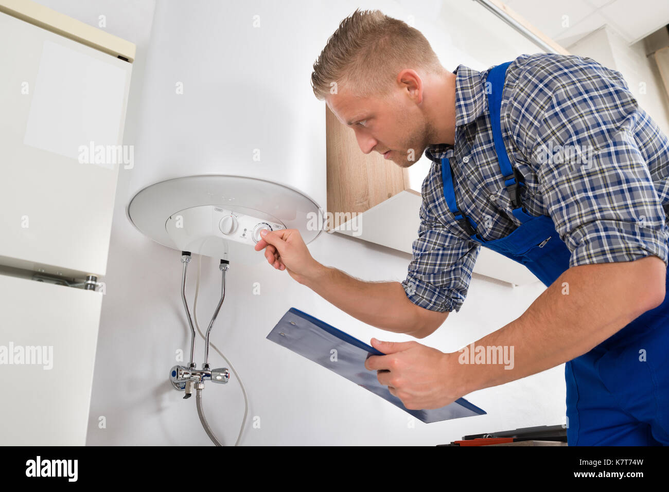 Male Worker With Clipboard Adjusting Temperature Of Water Heater - Stock Image