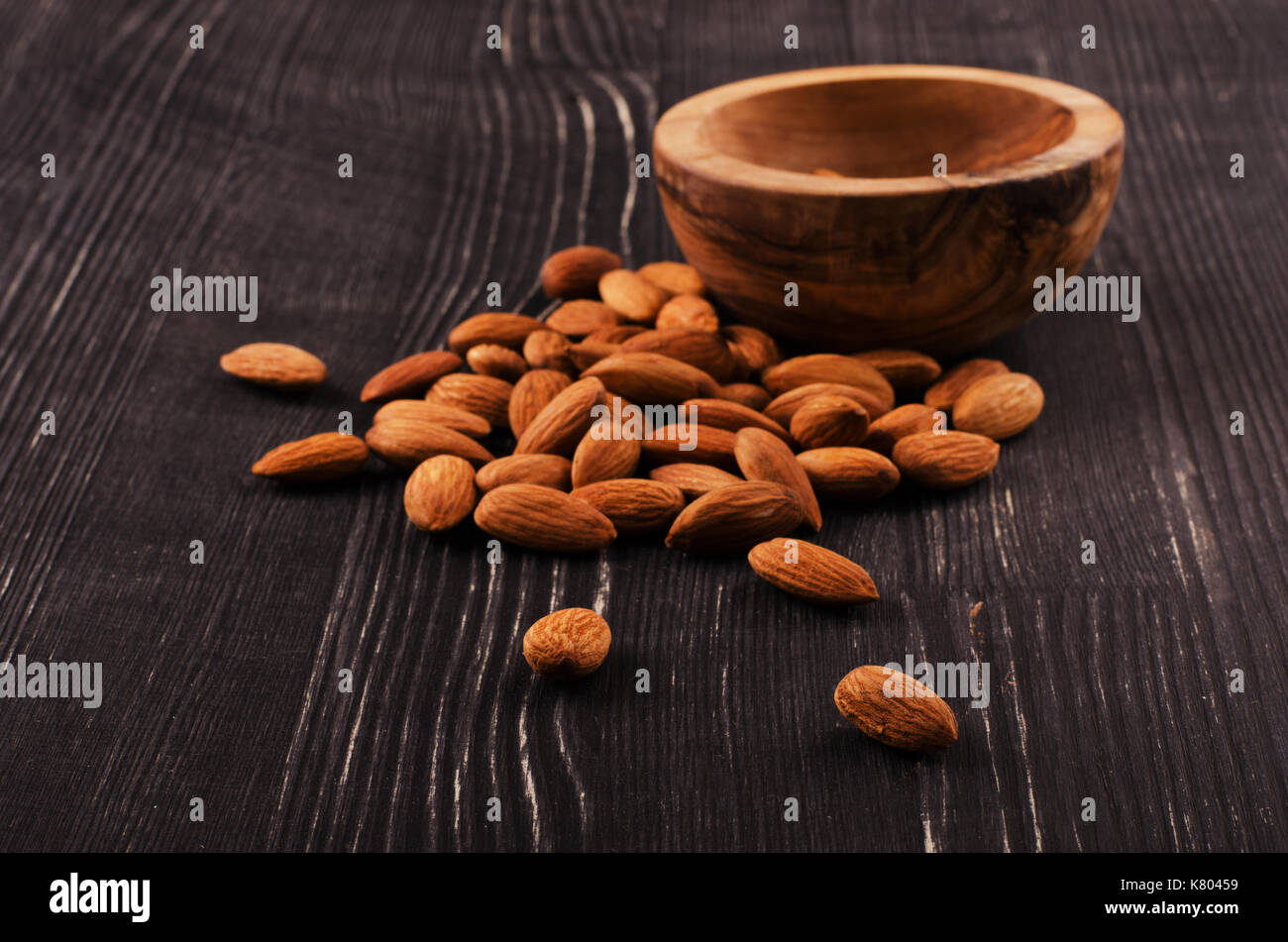 Almonds in brown bowl on wooden background - Stock Image