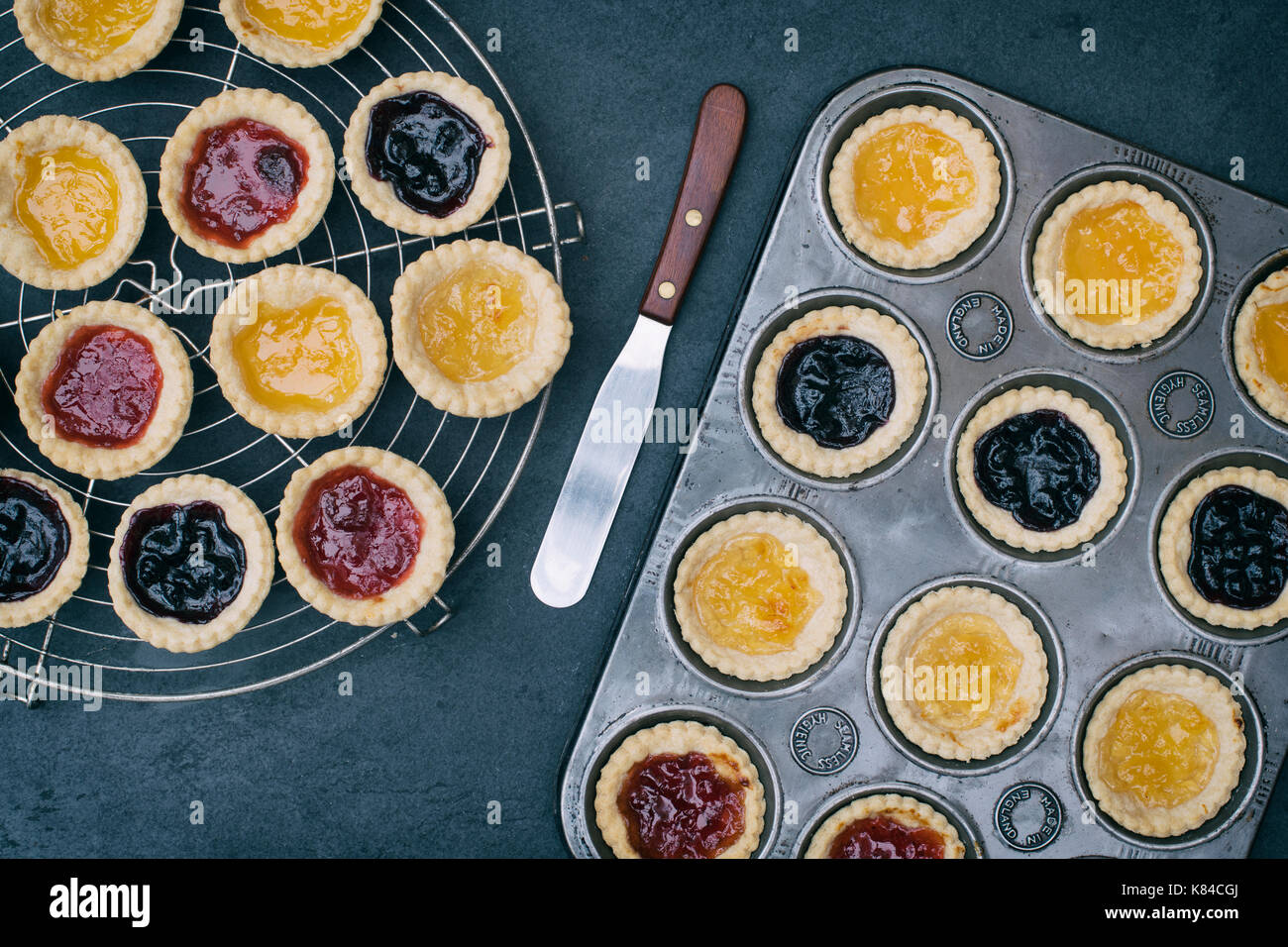 Cooked homemade jam tarts in a baking tray and on a vintage circular wire rack - Stock Image