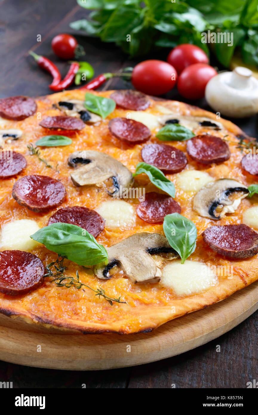 Tasty Italian pizza with salami, mushrooms, mozzarella, basil on a dark wooden table. Top view. - Stock Image