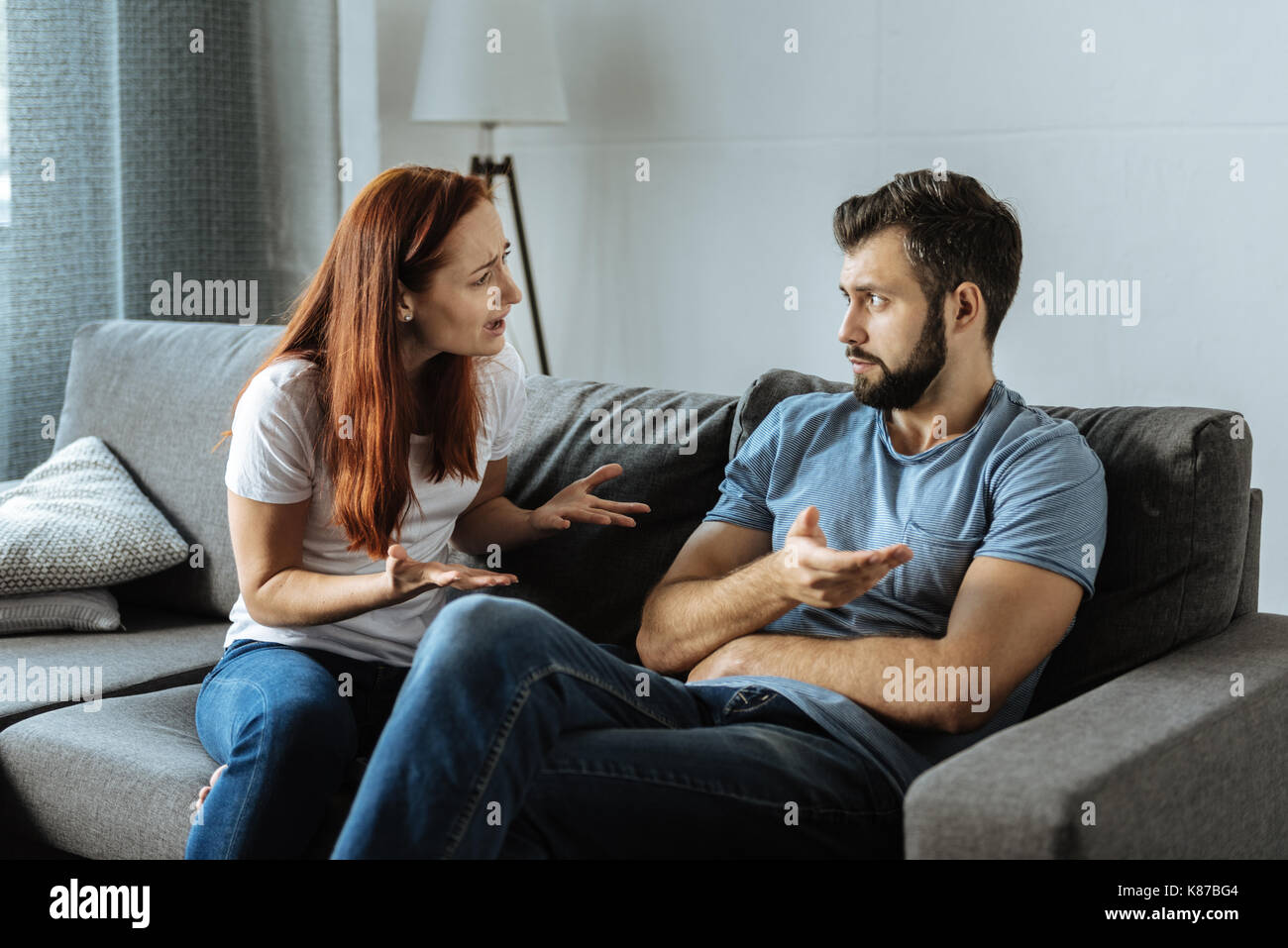 Unhappy emotional woman shouting at her boyfriend - Stock Image