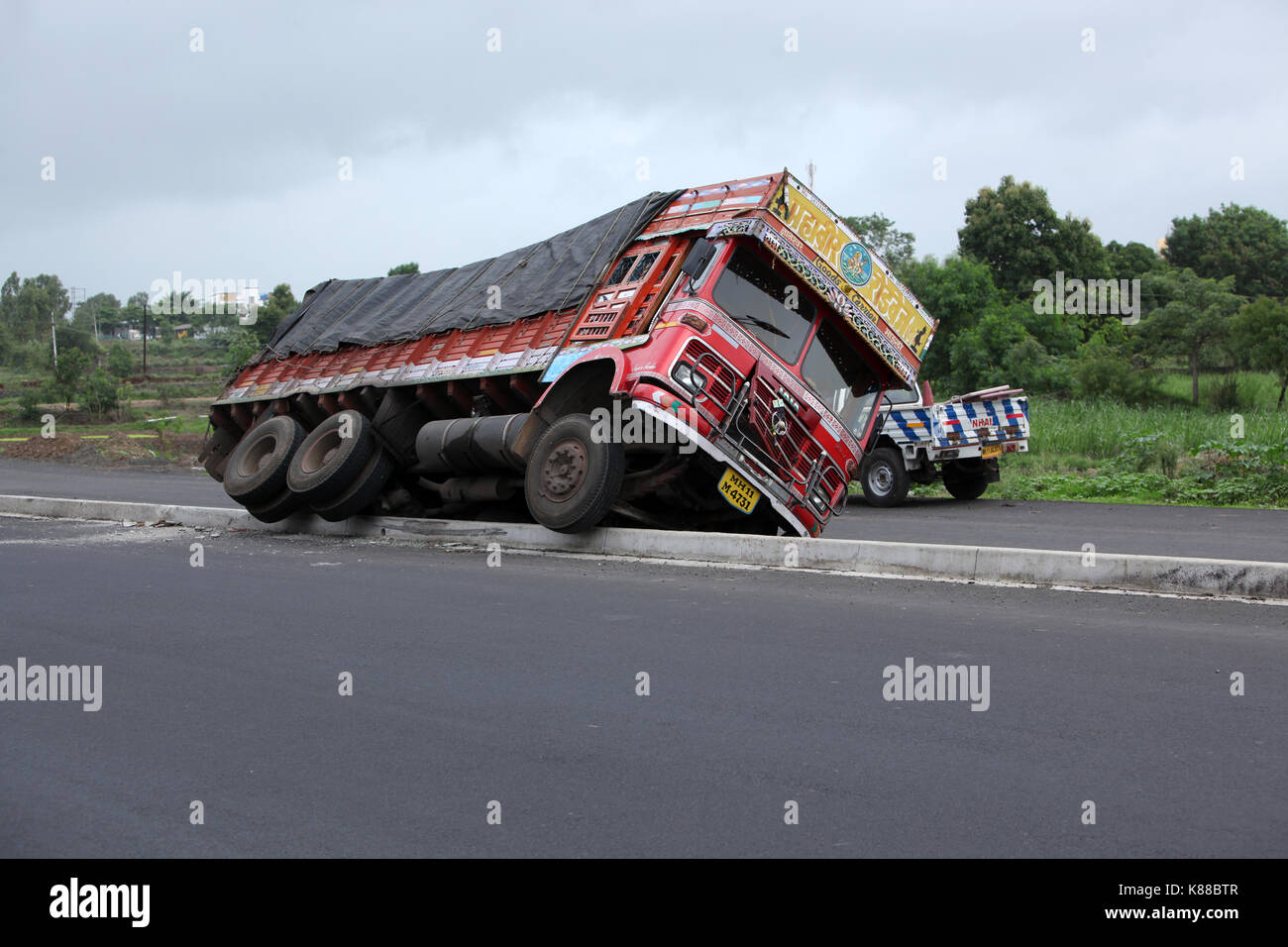 A truck toppled over on a highway in India due to speeding. - Stock Image