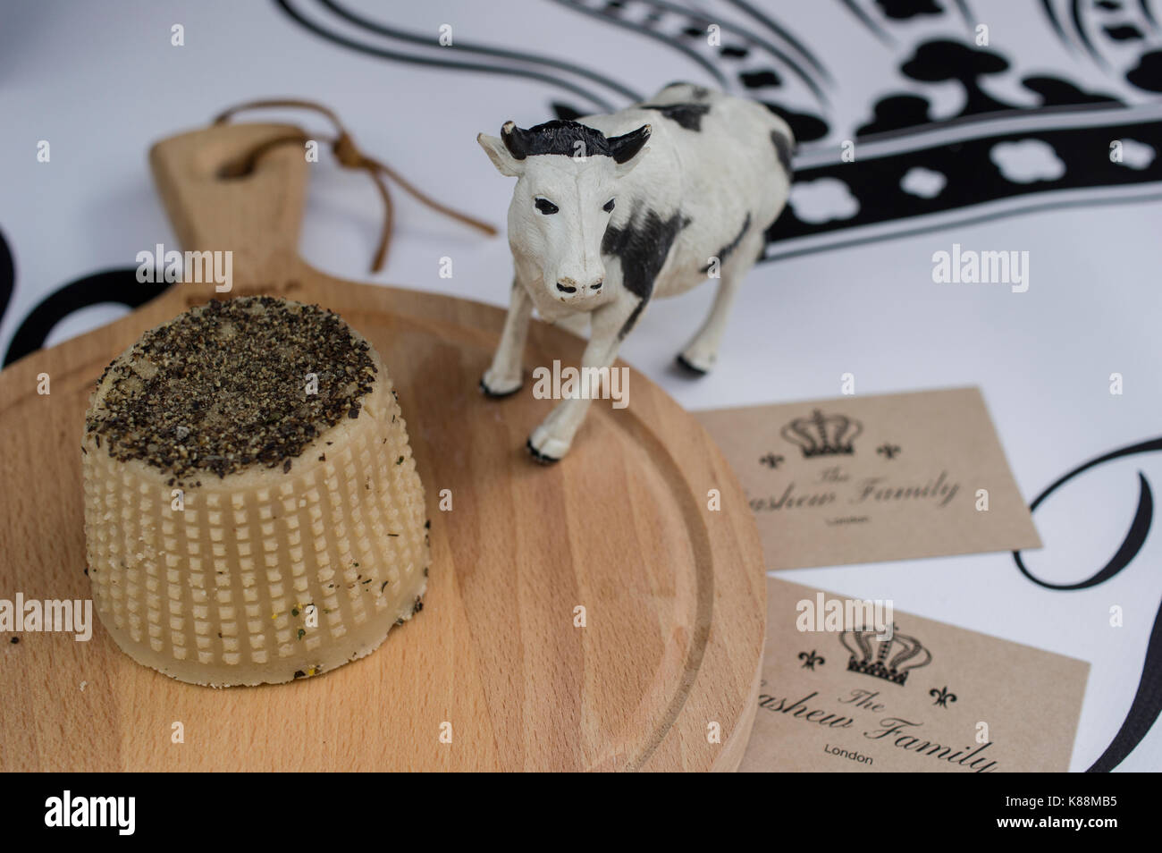 A small plastic black and white cow figurine guards the vegan fermented cashew cheese made by The Cashew Family - Stock Image