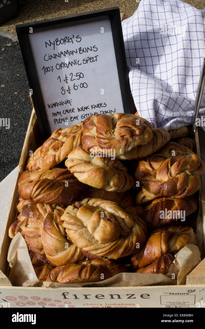 Swedish cinnamon buns 100 percent spelt on display in a London market on a bright sunny day - Stock Image